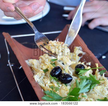 Traditional Portuguese cod fish on a casserole.