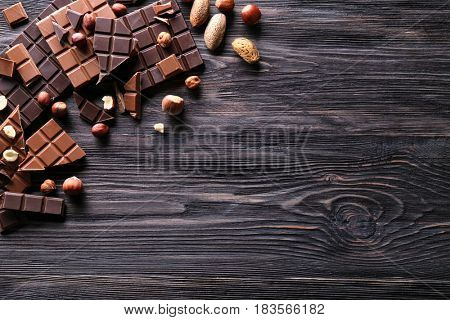 Chopped chocolate bars with nuts on wooden background