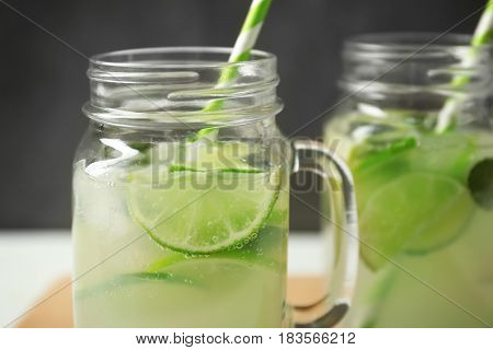 Glass jars of bracing cocktail with lime slices on dark background, closeup