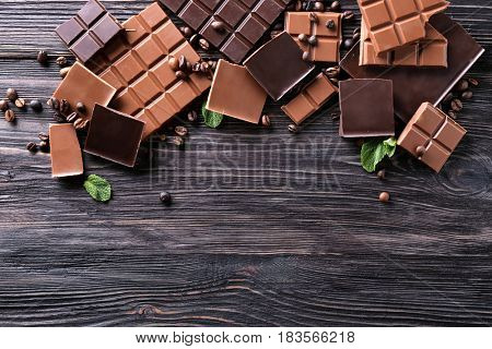 Chopped chocolate bars with coffee beans on wooden background