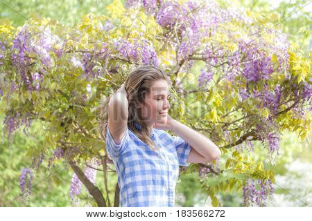 Spring beauty girl outdoors. Blooming Wisteria tree.