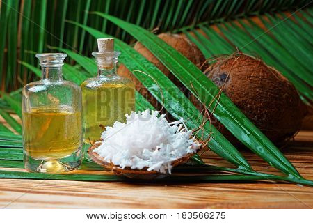 Glass bottles with oil, flakes in coconut rind and palm leaf on wooden background