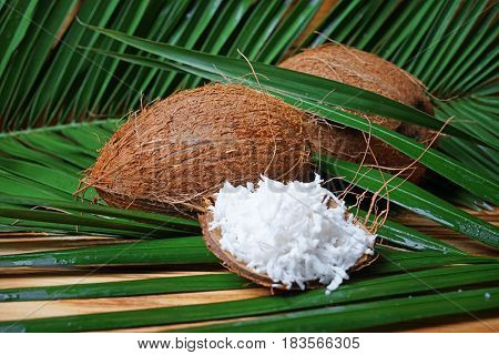 Fresh coconuts and flakes in rind on wooden background with palm leaves
