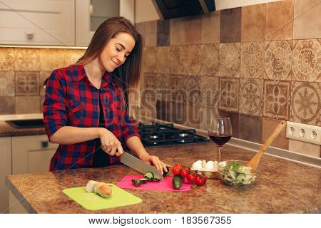 Portrait of smiling young housewife in modern kitchen. Woman cooking dinner.