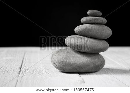 Five grey pebbles on wooden table. Zen and meditation concept.