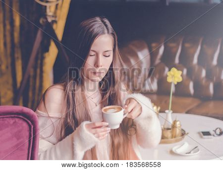 Beautiful girl drinking coffee in cafe. Young charming woman thinking about new ideas, drink a coffee, sitting on a lilac armchair in a modern city bar.