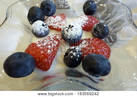 Blue blueberries and red strawberries in the cream cheese in a glass mold close up