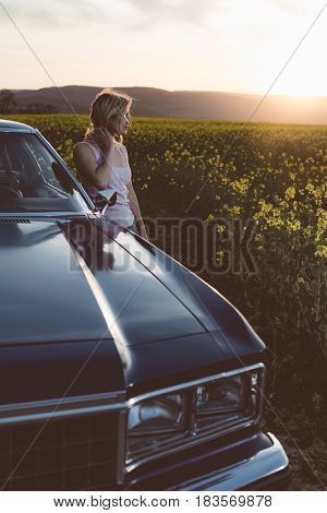 Young woman posing by vintage car at sunset