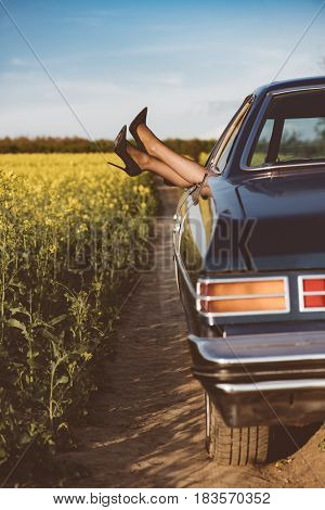 Freedom car travel concept - woman relaxing with feet out of window in cool vintage car.. Freedom, travel and vacation road trip concept lifestyle image