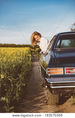 Freedom of the open road. Side view of joyful young woman relaxing on the front seat