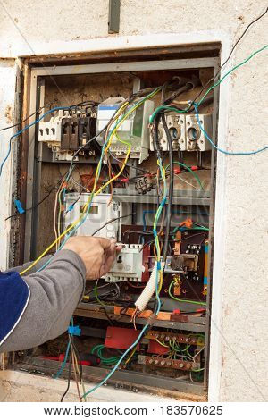 Repair of electricity distribution in an old house. The man repairs the switchboard