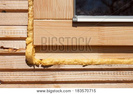 Foam window insulation on wooden construction. Building an eco-house. Heat insulation