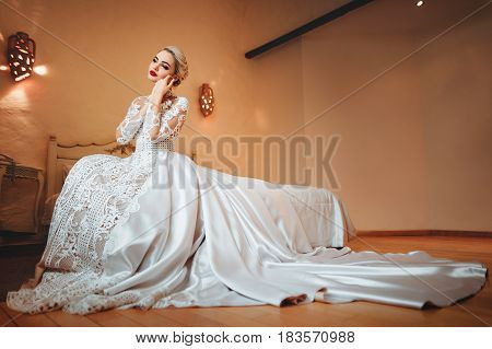 The bride in a white dress sitting on a bed in her room.