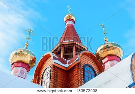 Domes with crosses on wooden orthodox church against the blue sky in Samara Russia