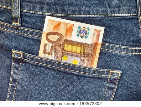 Banknote 50 euro sticking out of the jeans pocket. Money for travel and shopping