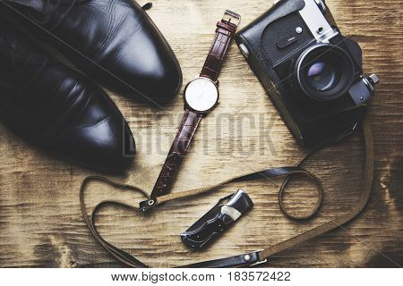 shoes watch wallet and camera on wooden background