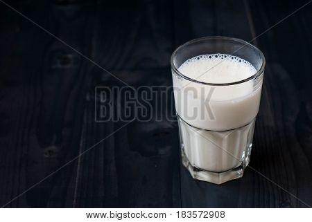 A glass of milk on a dark background. Milk in a glass cup on a dark wooden background. Just milk.
