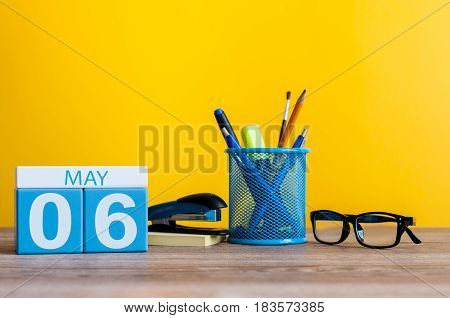 May 6th. Day 6 of month, calendar on business office table, workplace at yellow background. Spring time.