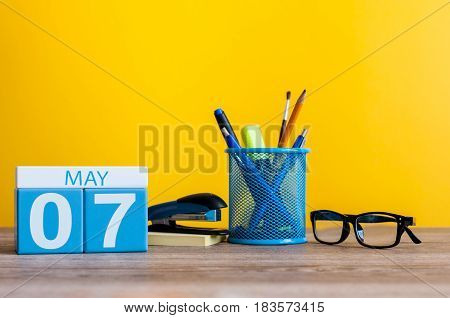 May 7th. Day 7 of month, calendar on business office table, workplace at yellow background. Spring time.