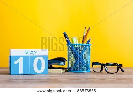 May 10th. Day 10 of month, calendar on business office table, workplace at yellow background. Spring time.