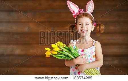 happy laughing child girl in bunny ears with bouquet of yellow tulips on wooden background