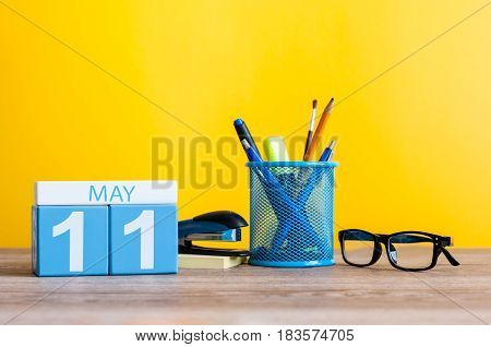 May 11th. Day 11 of month, calendar on business office table, workplace at yellow background. Spring time.