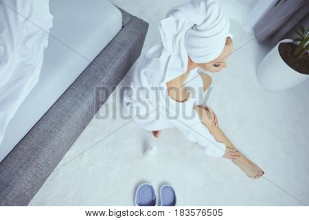 Pretty blonde using body cream on bed at home