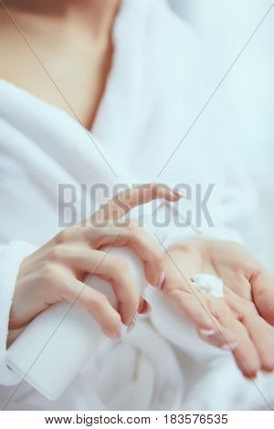 Cropped image of beautiful young woman applying hand cream while sitting on bed at ho