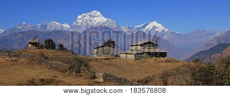 Autumn day in the Himalayas. Seventh highest mountain of the world Dhaulagiri. Old stone house and shed.