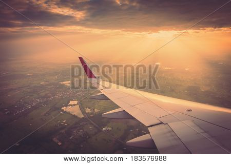 Wing of an airplane flying above the clouds at sunset ( Filtered image processed vintage effect. )