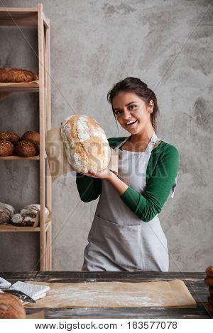Image of smiling young lady baker standing at bakery holding bread. Looking at camera.