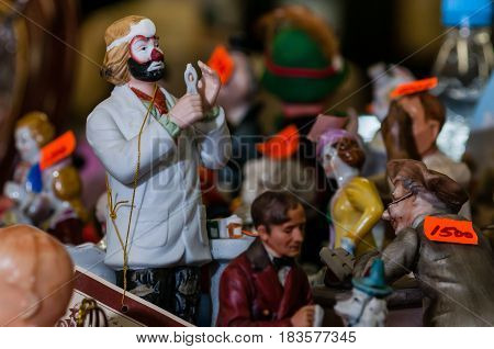 Moscow, Russia - March 19, 2017: Old antique porcelain and ceramic figures for sale on the flea market. Toy and collectibles. Selective focus on sad clown figure
