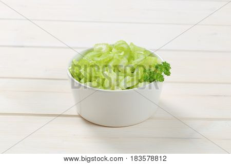 bowl of chopped celery stems on white wooden background
