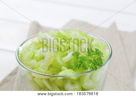 glass of chopped celery stems on beige place mat - close up