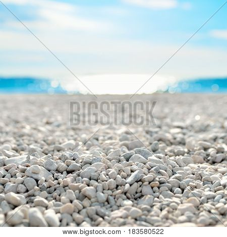 On the Beach by the Sea - beautiful white pebble beach at the mediterranean coast on a beautiful day
