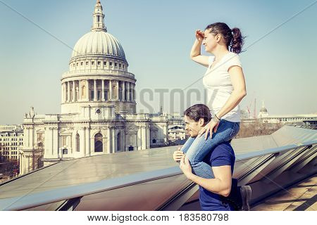Girl On A Friend's Shoulder Looks Towards The City From A Terrace