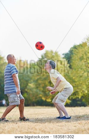 Two active senior friends playing soccer with ther head