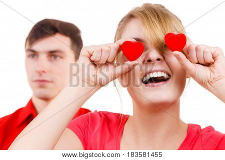 Couple. Serious boyfriend and his crazy playful girlfriend holding red hearts over eyes. Valentines day or unrequited love concept.