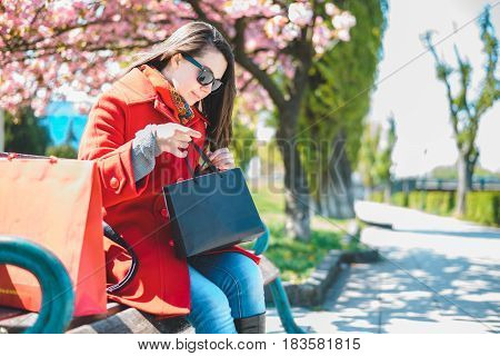 Young beautiful woman sitting on a bench in a city center with her shopping bags under blooming sakura