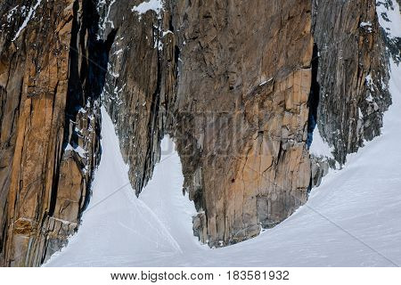 Rockface In Mountain Range In Winter With Climbers On Wall