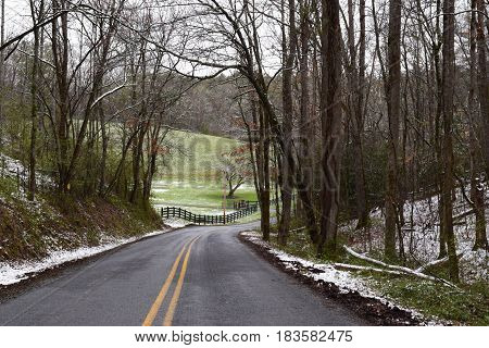 Meandering road from the woods into a grassy valley with a slight dusting of snow in early Spring.