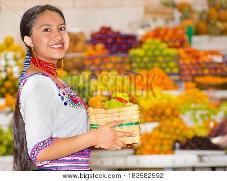 Beautiful young hispanic woman wearing andean traditional blouse posing for camera holding basket of fuits inside fruit market, colorful healthy food selection in background.