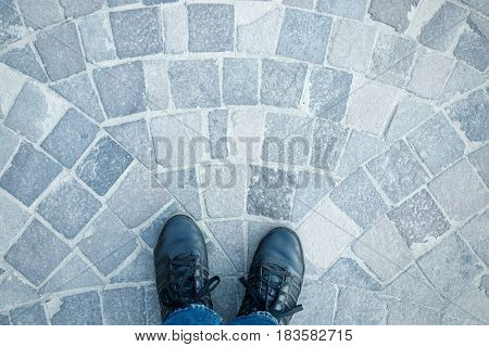 Men's legs in sneakers and jeans top view on the pavement cobbles