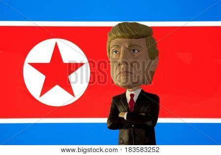 Bobble Head caricature of United States President Donald Trump standing in front of the flag of Democratic People's Republic of Korea also known as North Korea