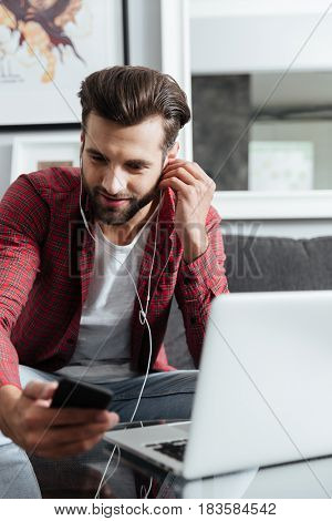 Serious young man in head phones using phone sitting on couch