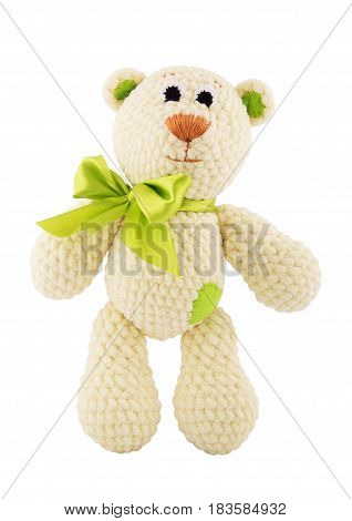 Plush knitted teddy bear with a green bow. Soft toy. Isolated on white.