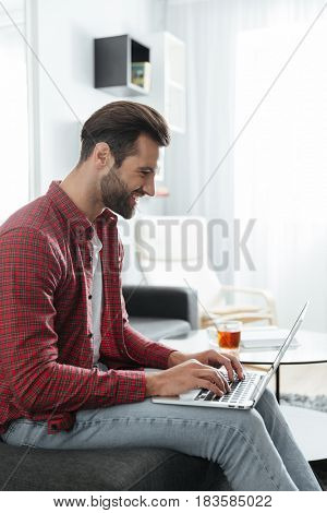 Photo of smiling young man sitting on sofa indoors at home while using laptop computer. Looking aside.
