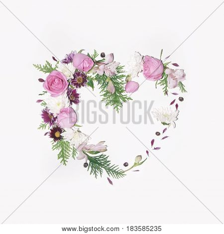Floral heart frame on a white background (chrysanthemums flowers roses thuja twigs alstroemeria daisies)