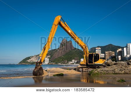 Rio de Janeiro, Brazil - April 6, 2017: Excavator builds a beach on the sea shore in Ipanema.