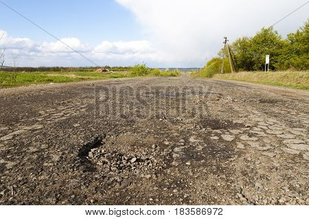 Damaged rural road cracked asphalt blacktop with potholes and patches. Poor quality of road repair work.